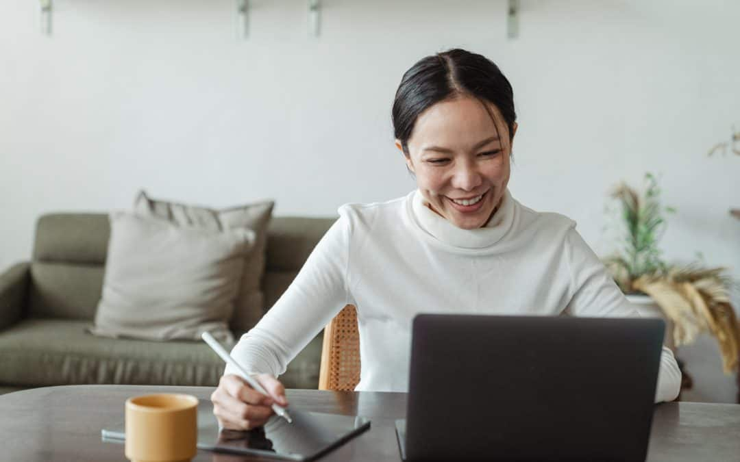 How to manage your remote team - happy woman at desk with laptop